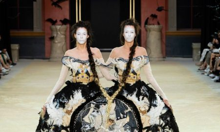 Two models walk conjoined with their arms around one another in a double dress at the Guo Pei fashion show