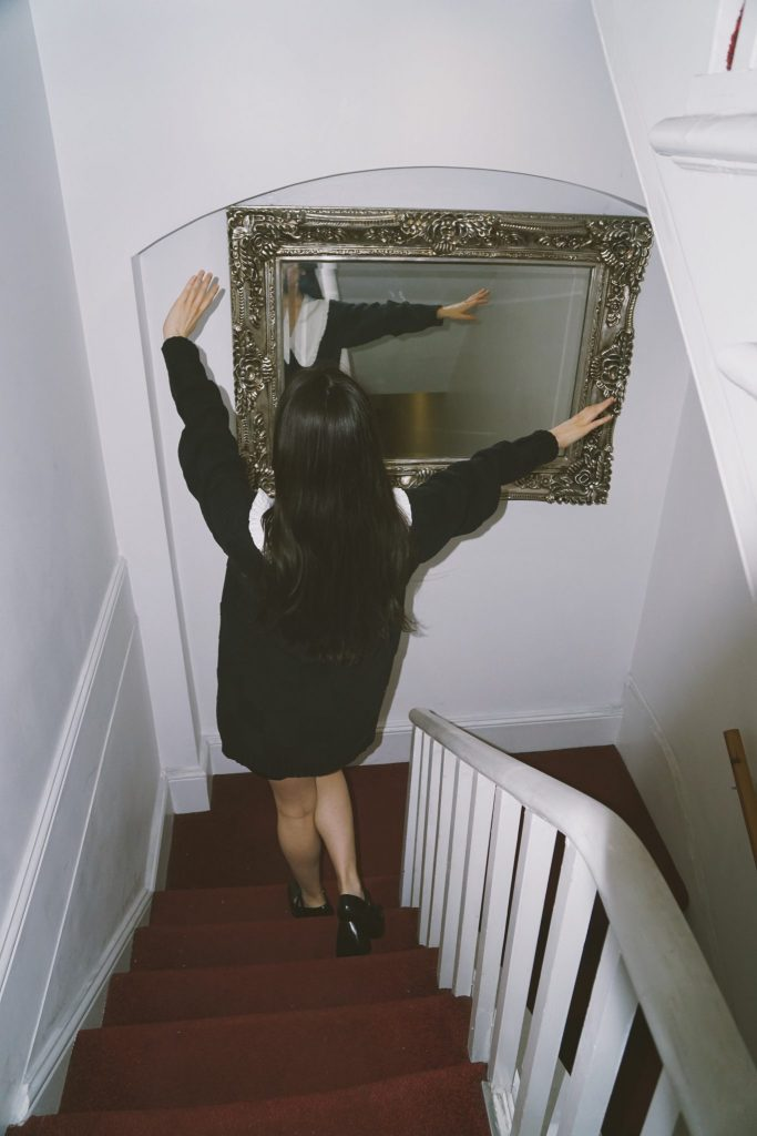 Image of a girl walking down the stairs with her hands in the air, there is also a vintage mirror