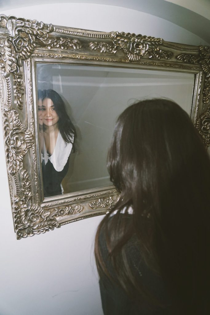Image of a girl wearing a black dress smiling at her reflection in the mirror