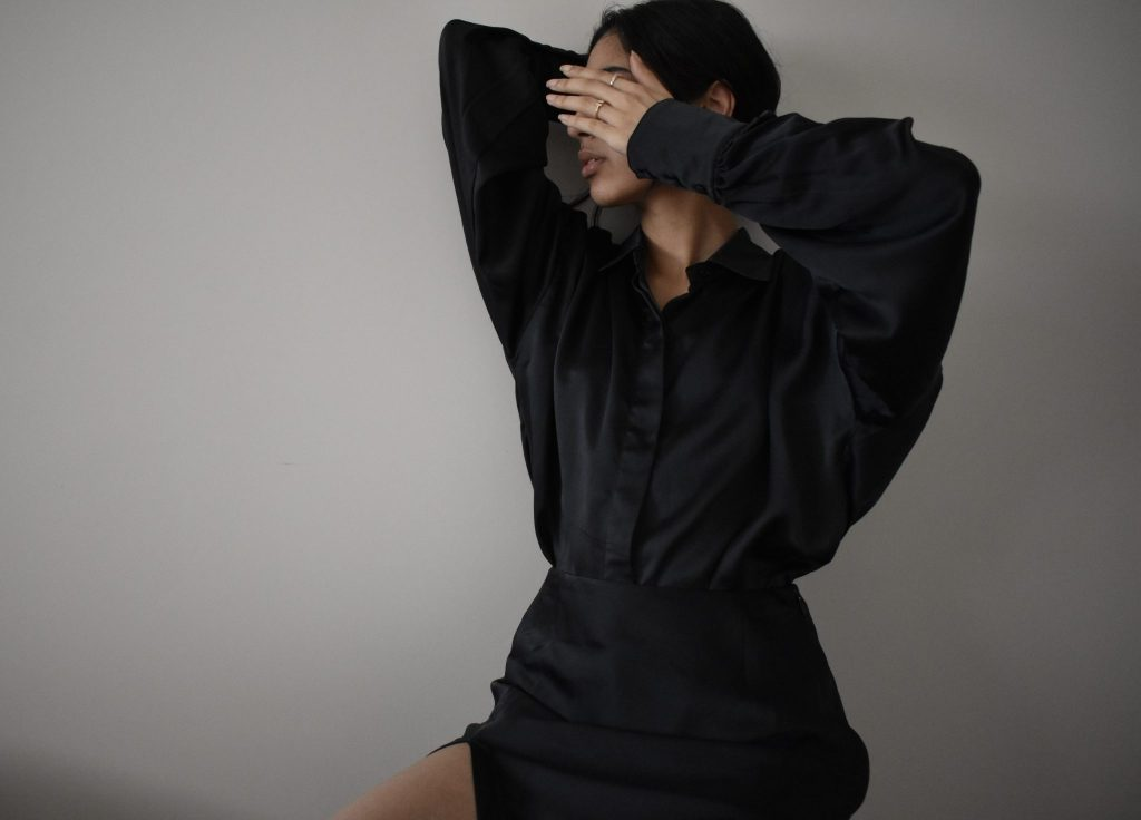 Image of a girl sitting, wearing a black silk shirt and skirt. She is holding her hand up to her face to block it from view