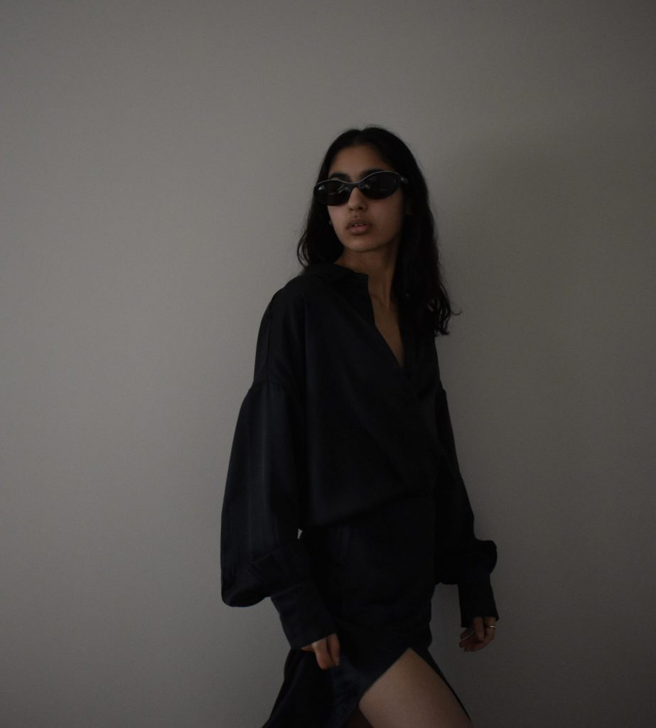 Image of a girl wearing black sunglasses and outfit, looking off to the side